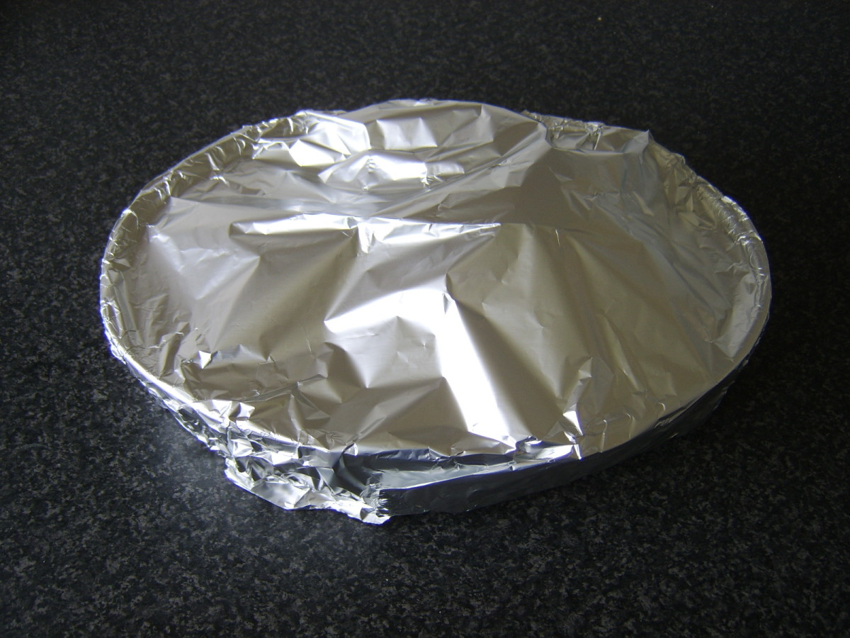 Pork shank is covered with foil for roasting