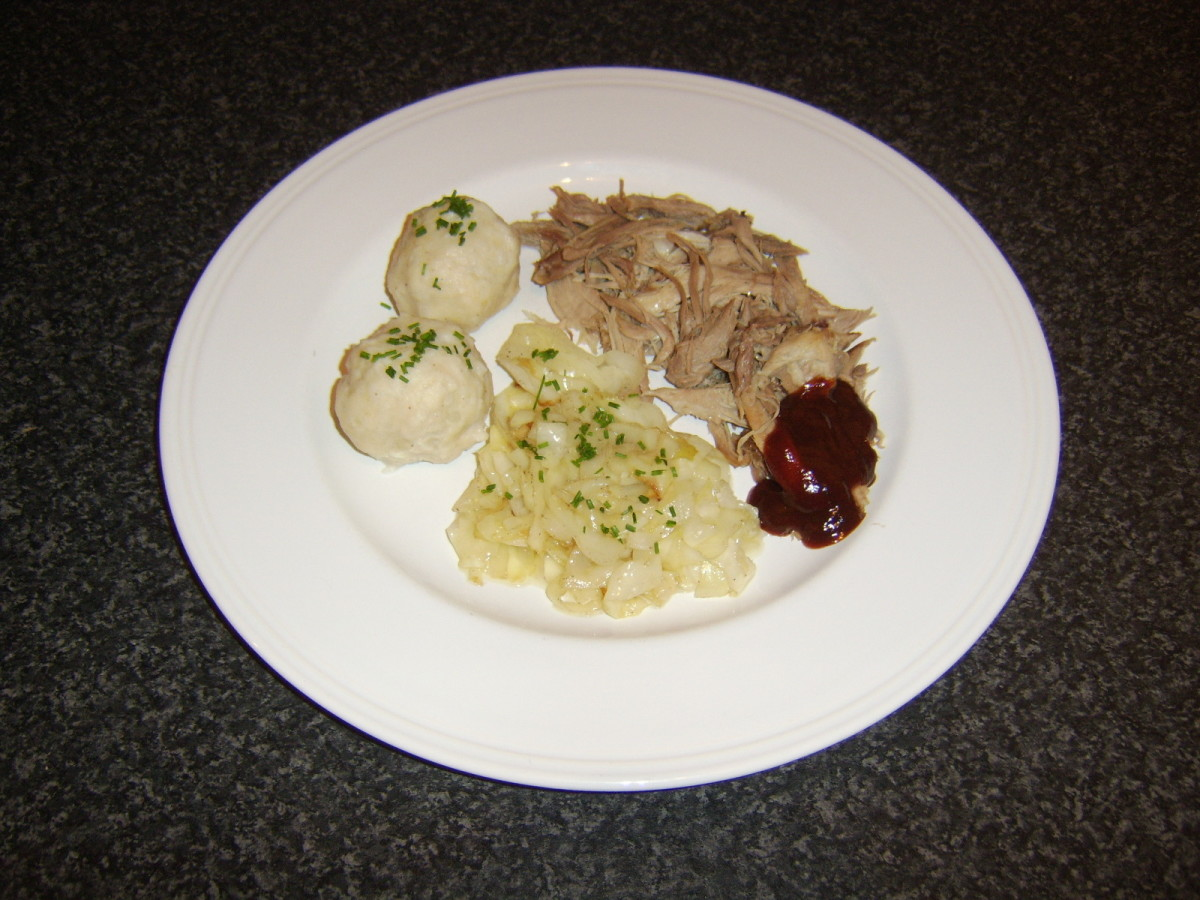 Pulled pork is taken from the popular Bavarian cut of pork that is the shank or knuckle and served with authentic German potato dumplings and braised cabbage instead of sauerkraut