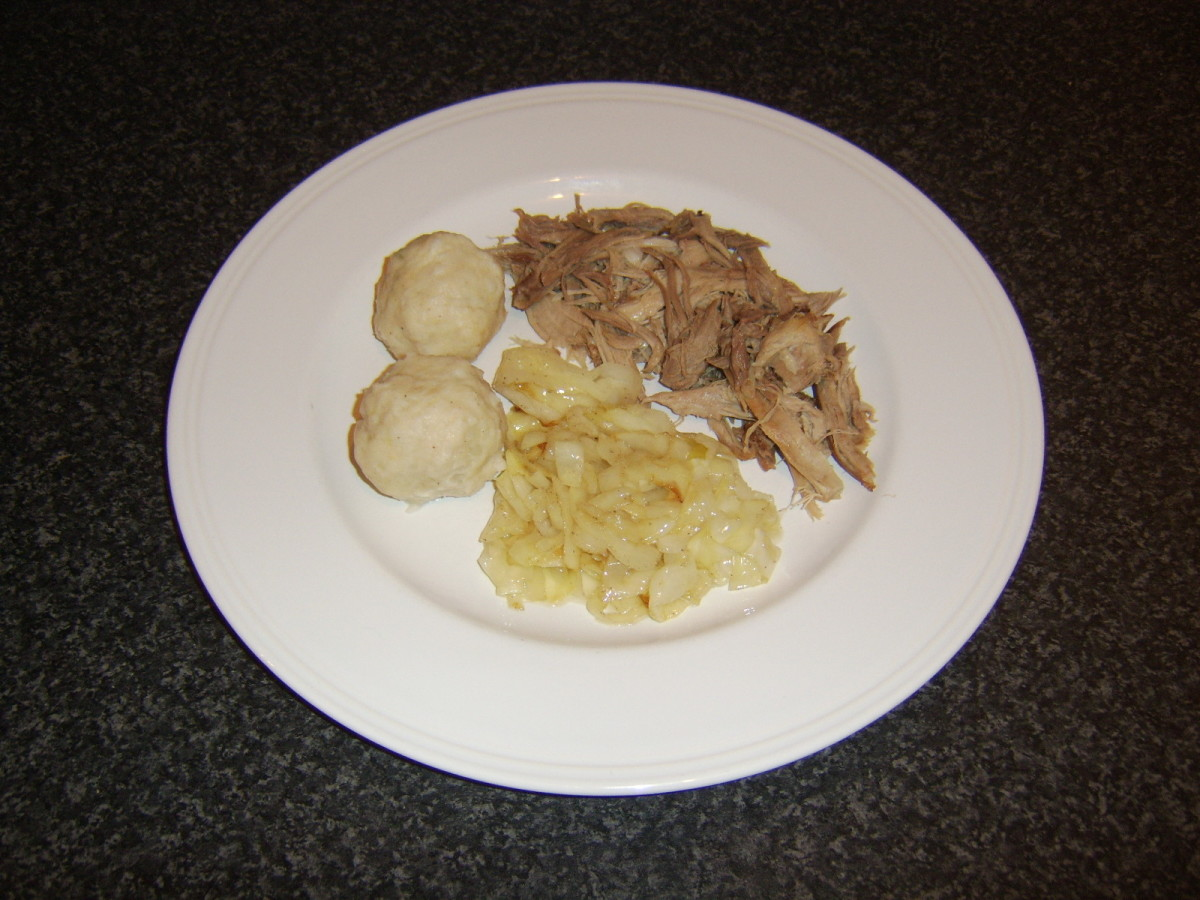 Pulled pork, potato dumplings and cabbage are arranged on serving plate