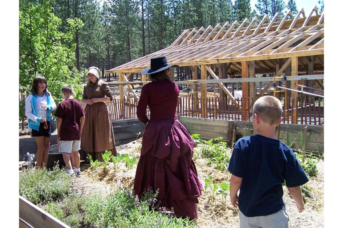Museum volunteers in period dress show children what its like to pump water and tend to crops at the High Desert Museum (c) Stephanie Hicks