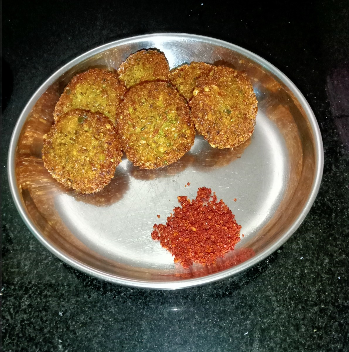 Crispy moong kebabs served with red coconut chutney.