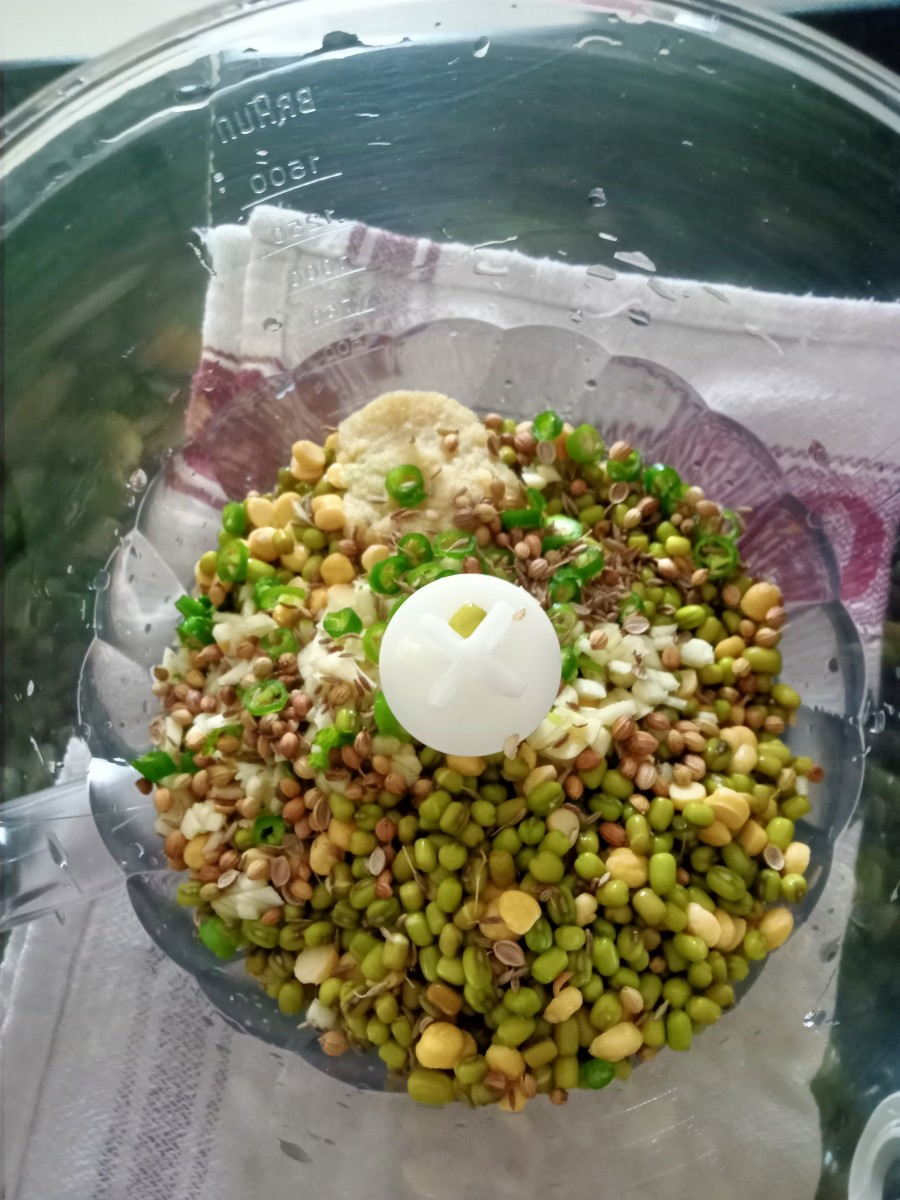 In a chopper jar, take soaked green moong and chana dal. Add chopped garlic, chopped green chillies, cumin seeds, coriander seeds, and ginger-garlic paste. Chop to a coarse paste.