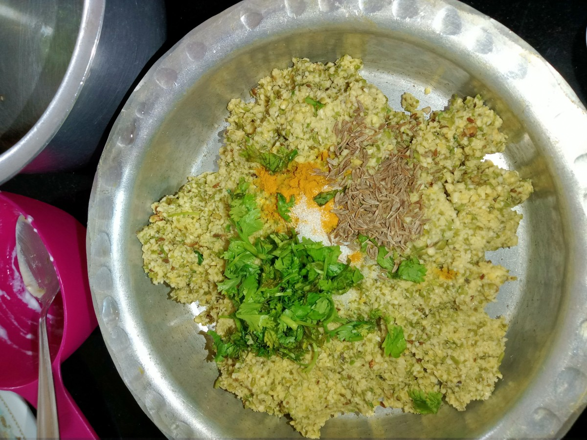 Transfer to a container and add salt, turmeric powder, cumin seeds, and chopped coriander leaves.