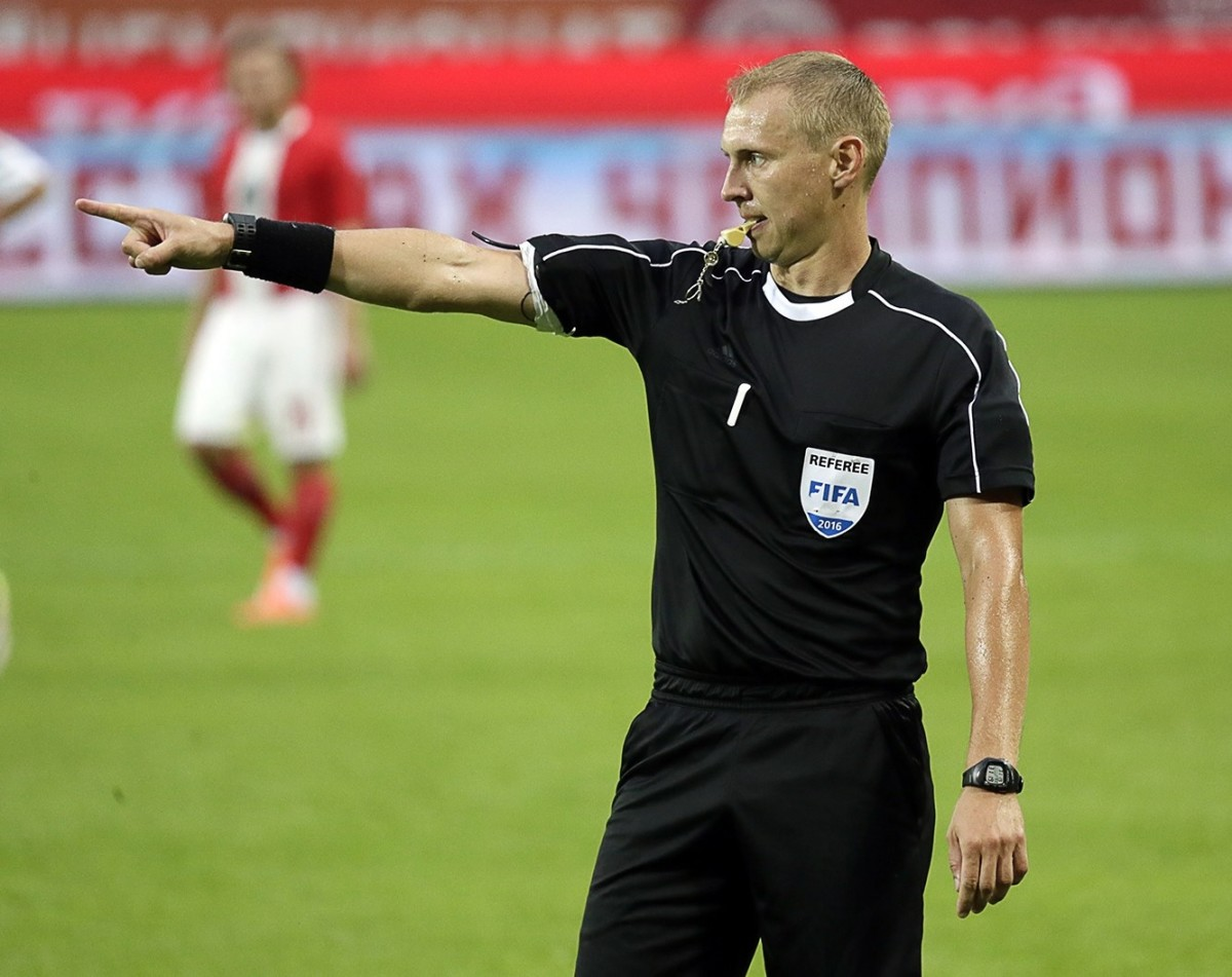The referee points to the corner to signal a corner kick.