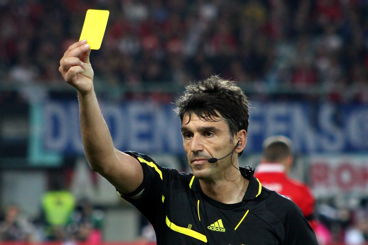 The referee gives out a yellow card as a warning for bad fouls or rulebreaking.