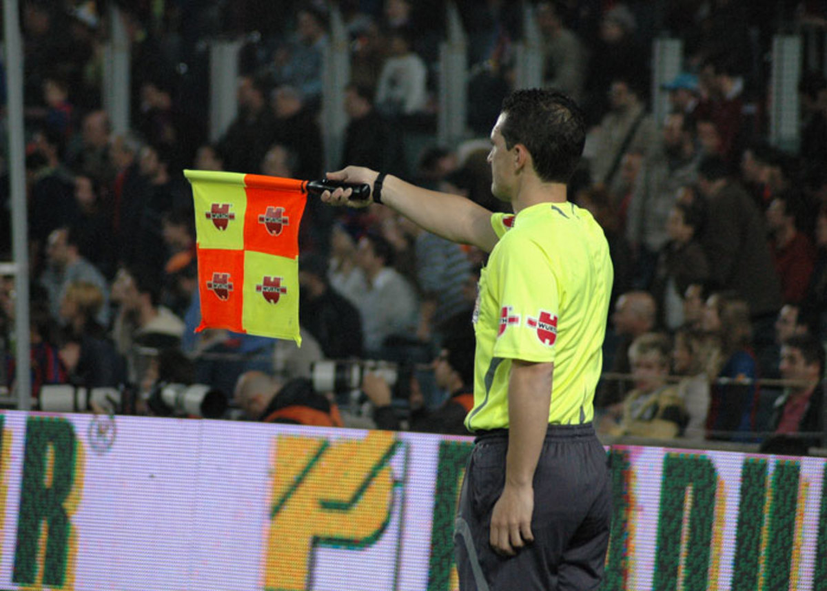 The assistant ref will point with the flag to show which direction to play the ball after it goes out.