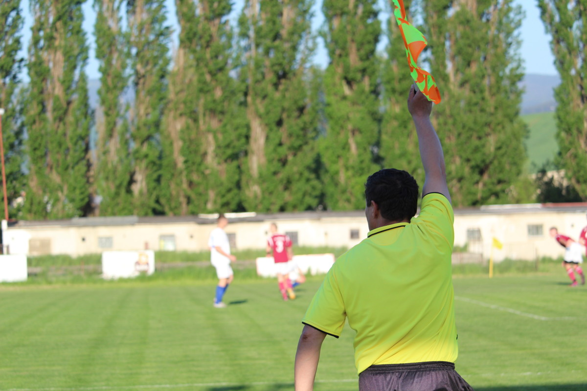 The assistant ref raises their flag to indicate an offside.