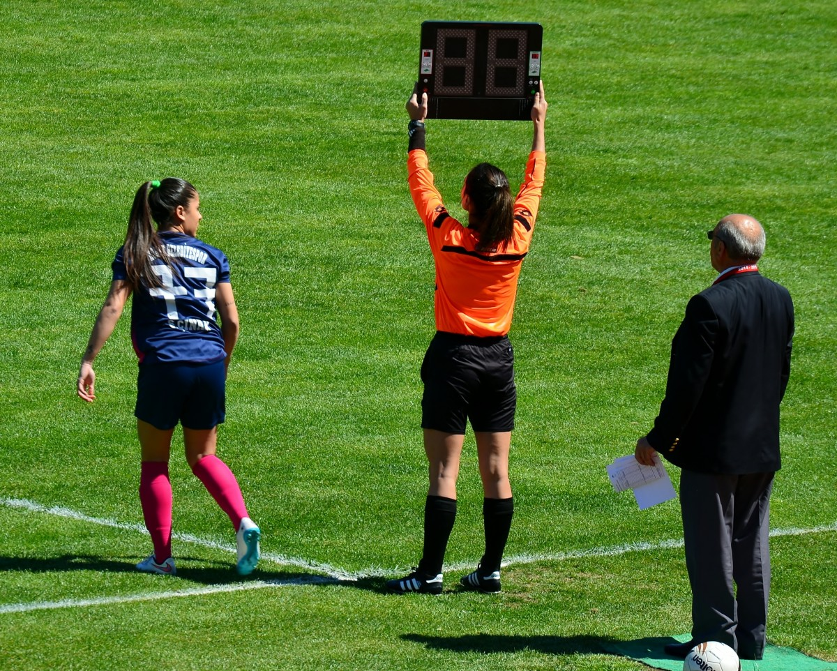 The match official will raise a board that shows the numbers of the players being substituted. At the end of each half, they'll use this board to show the added time.