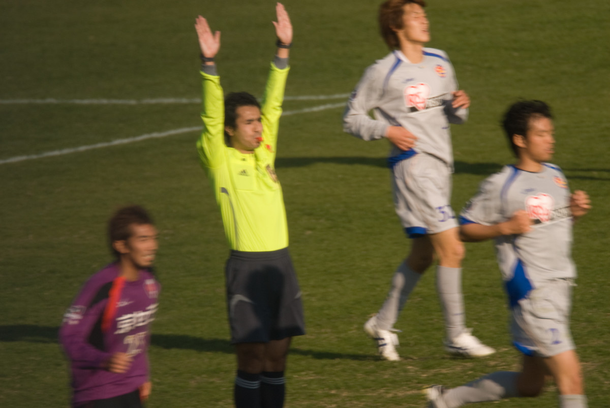 The referee raises both hands to signal that a goal has been scored. They might also use this signal to recognize events like PK saves.