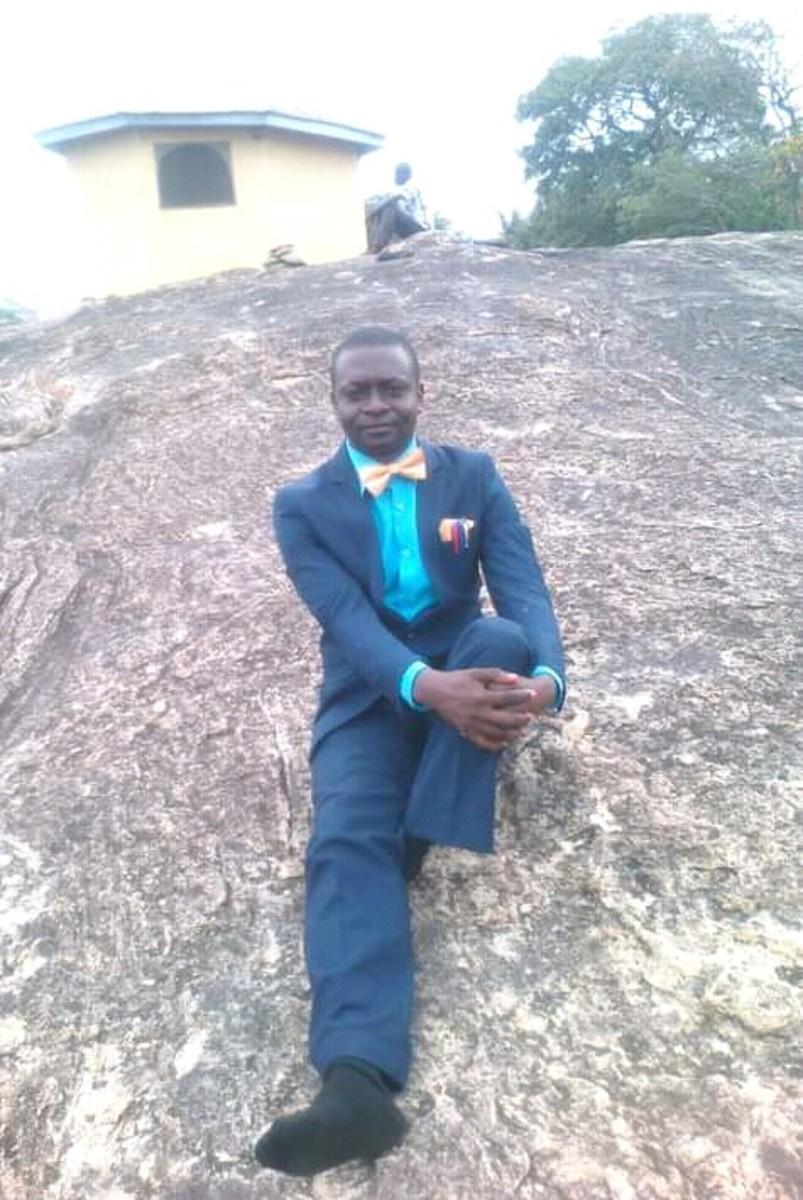 OGUNDARE OLUSEGUN sitting on a rock, Adetunji, Oyo State, Nigeria.