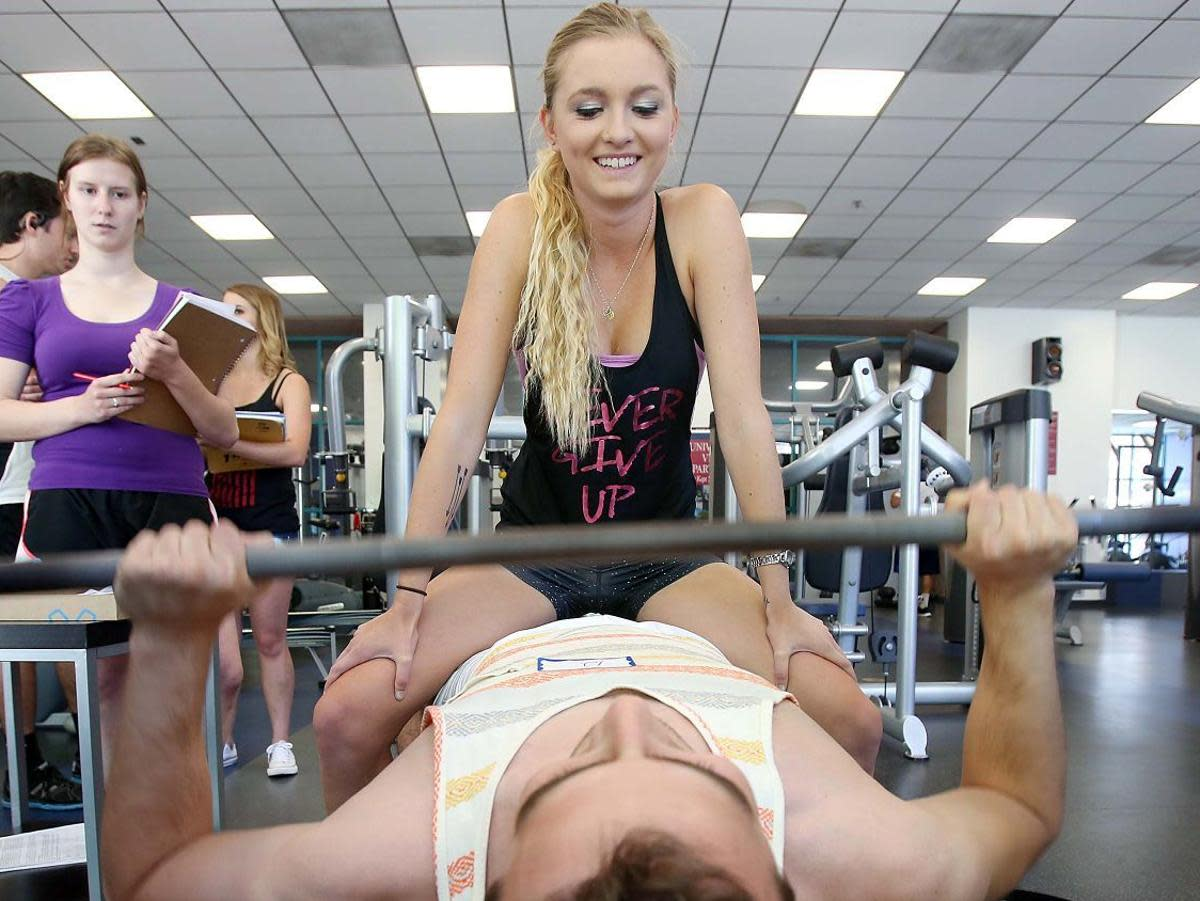 Maggie Phillips, a UA student sits on Michael McDonough as he bench presses as part of a UA clinical trial. The  clinical trial  found that men can do one more rep bench pressing when a woman is sitting on his lap. (Probably Testosterone related)