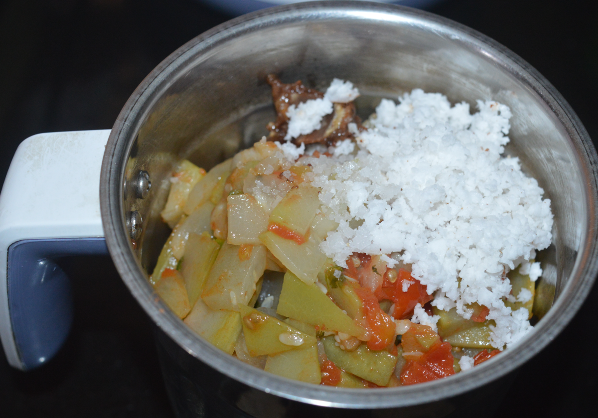 Step four: Transfer the mixture to a mixer jar. Add grated coconut, tamarind pulp, and remaining salt.