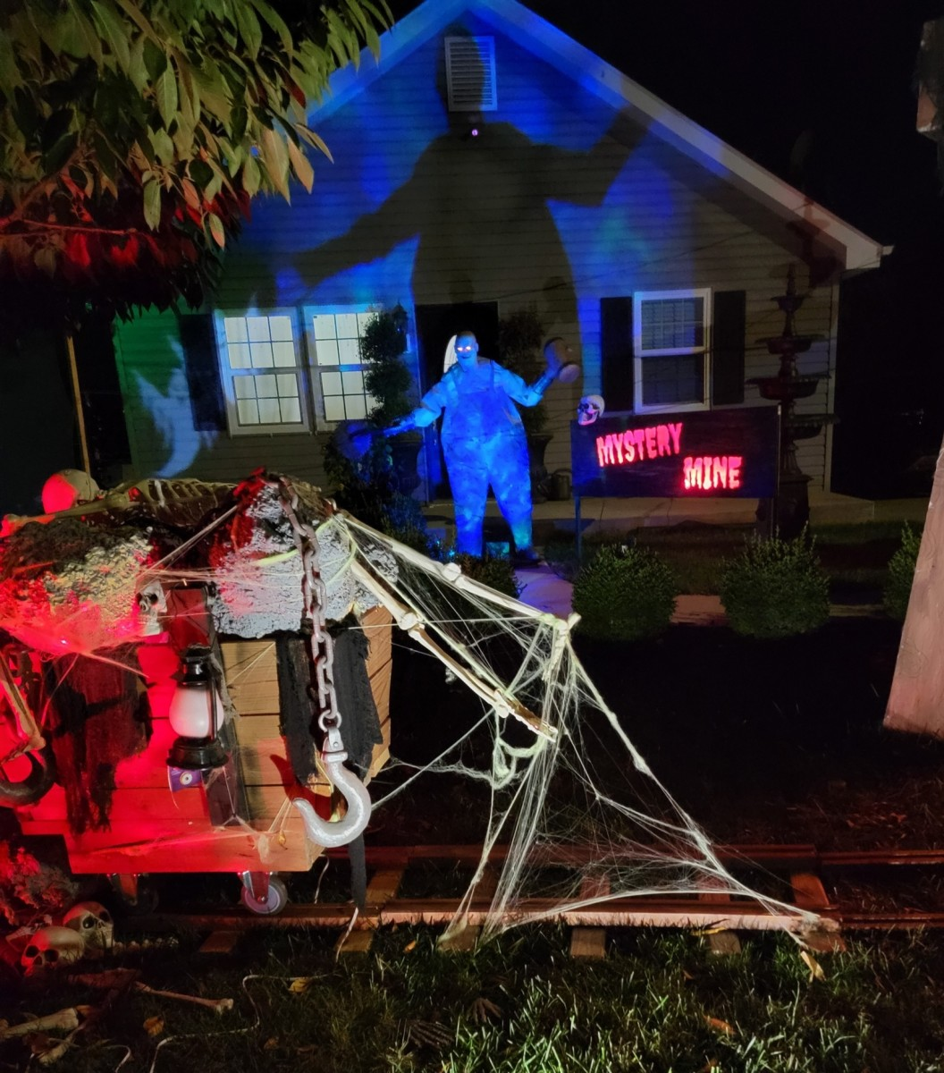 Some friends decorated their yard with a spooky mine scene complete with railroad tracks, a mine shaft, and a creepy character with a chainsaw.