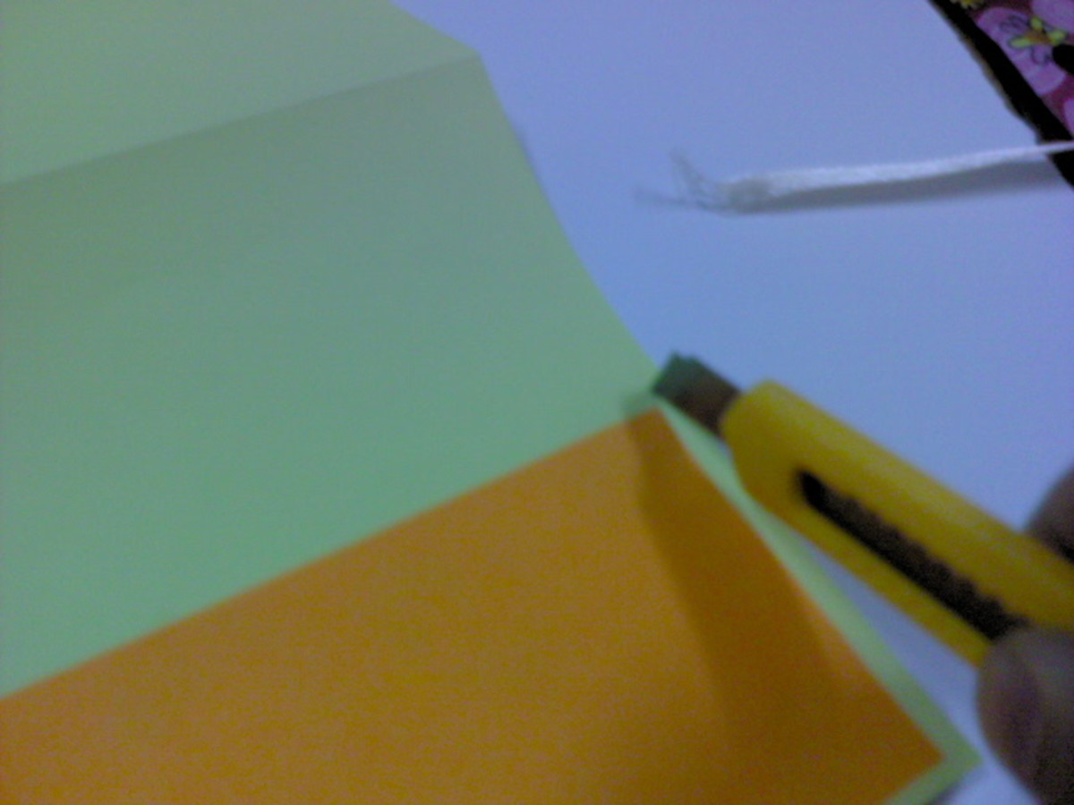 Make a small slit at the right hand and left hand side of the orange paper