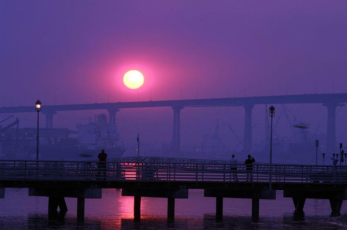 Coronado Ferry and the sun rise over the Coronado Bay Bridge.