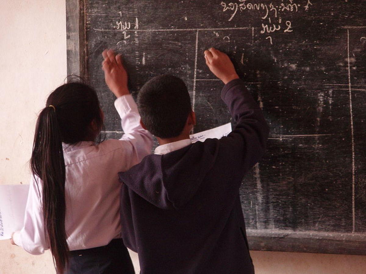 Pupils writing on the blackboard in a village school in Laos