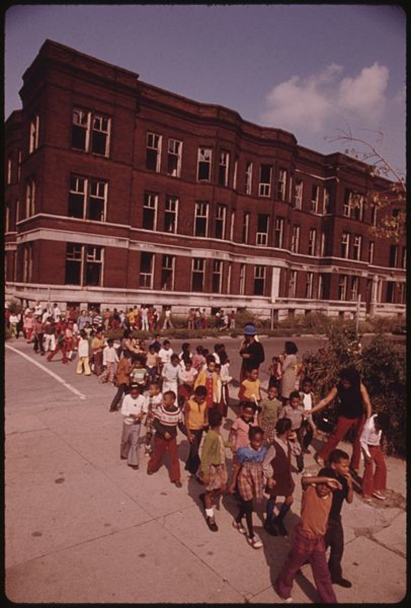 YOUNGSTERS RETURNING TO CLASS FOLLOWING A FIRE DRILL IN A CHICAGO ELEMENTARY SCHOOL. FIRE DRILLS ASSUME A GREATER IMPORTANCE IN THE GHETTO SCHOOLS WHERE AREA BUILDINGS ARE MORE VULNERABLE TO VANDALISM AND FIRE. NOTE THE VACANT BUILDING WITH BROKEN WI
