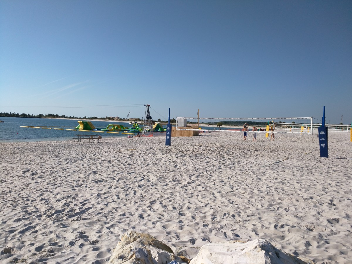 Wide shot of sandy Beachfront, Floating Inflatable Playground and Beach volleyball courts