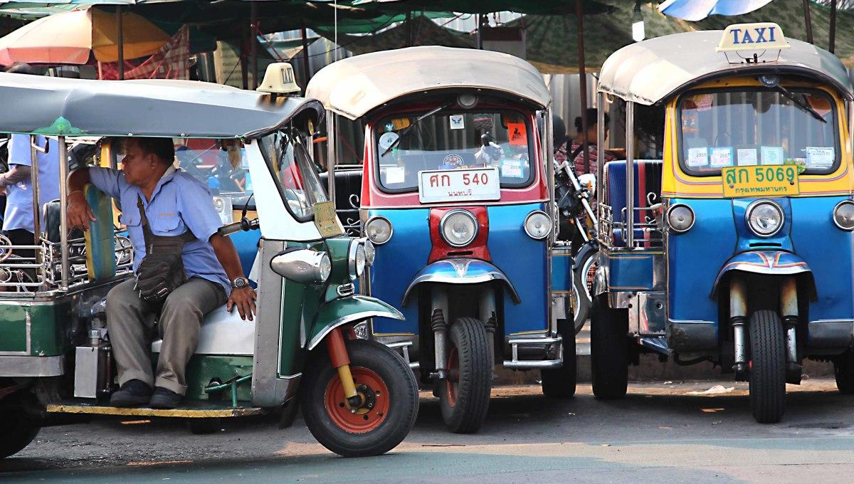A tuk-tuk driver patiently awaits his next fare