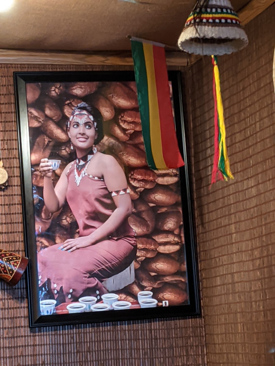 Poster of a model drinking coffee with backdrop of coffee beans.  Coffee supposedly originated in Ethiopia and is one of its major exports