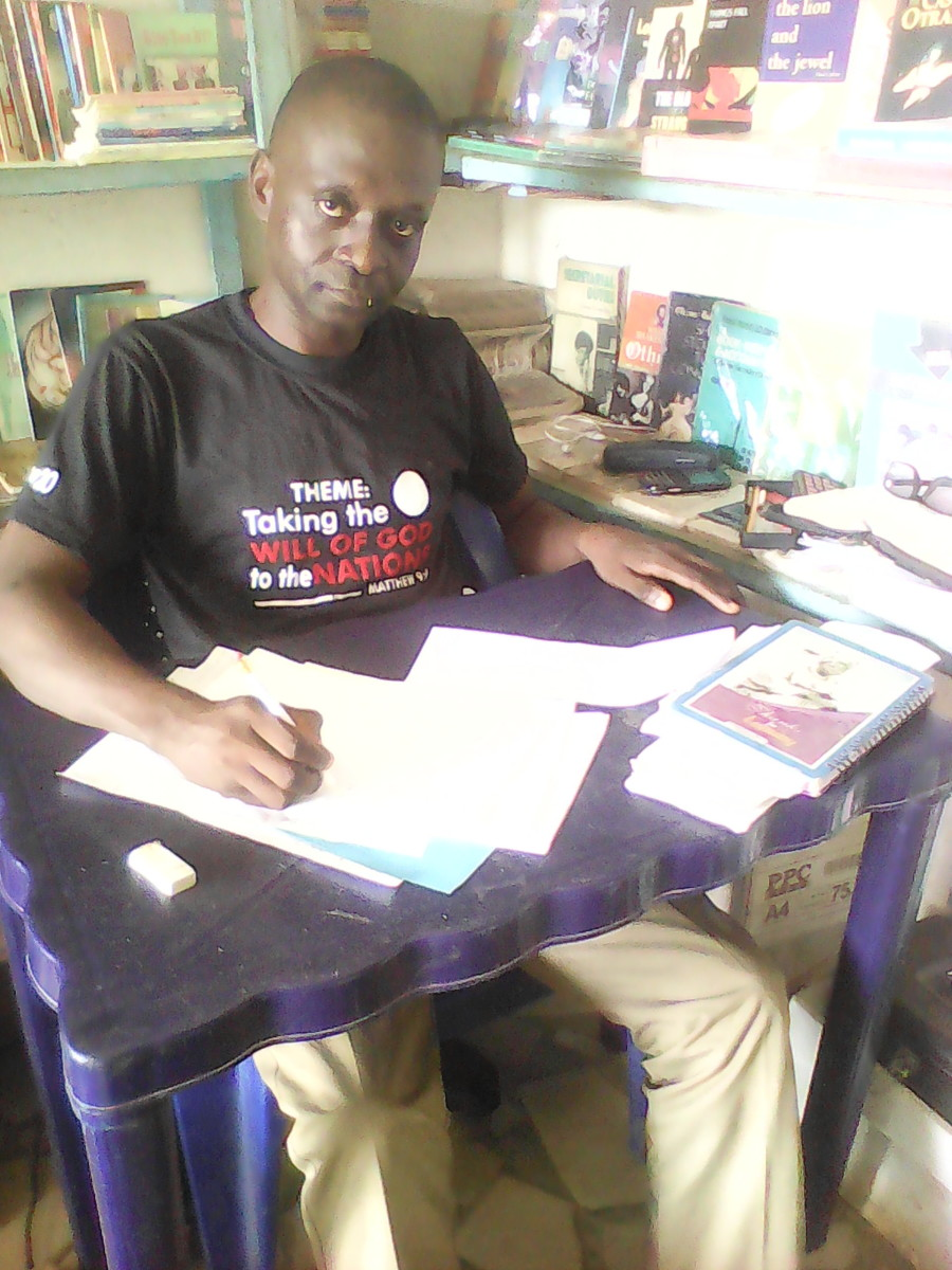 Olusegun at his writing desk in his shop