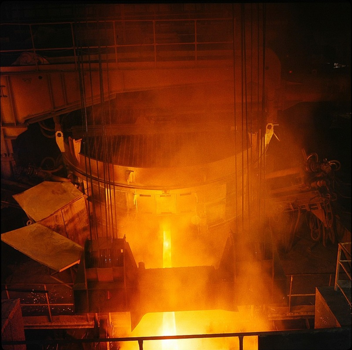 An electric arc furnace (the large cylinder) being tapped at a steel mill.