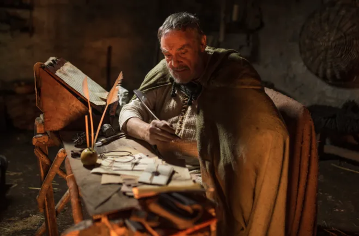"John Rhys-Davies (from Lord of the Rings) as Bishop Patrick writes a letter in the docudrama ""I Am Patrick"" via Fathom Events"