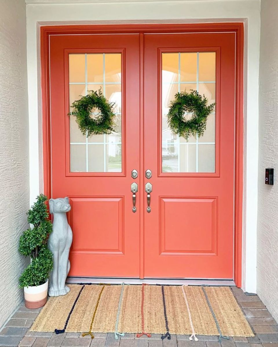 A splash of coral color during the year is a pleasant way to make your home feel bright and welcoming. The very coral double doors make a big statement, and they look great with natural potted greenery and jute rugs.