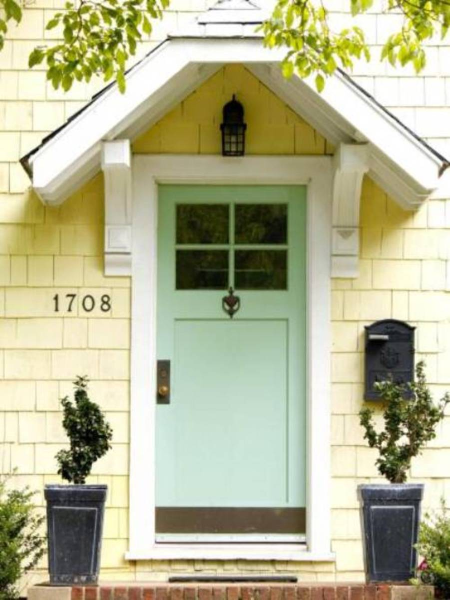 The cottage front door with the pale Jordan-almond color.
