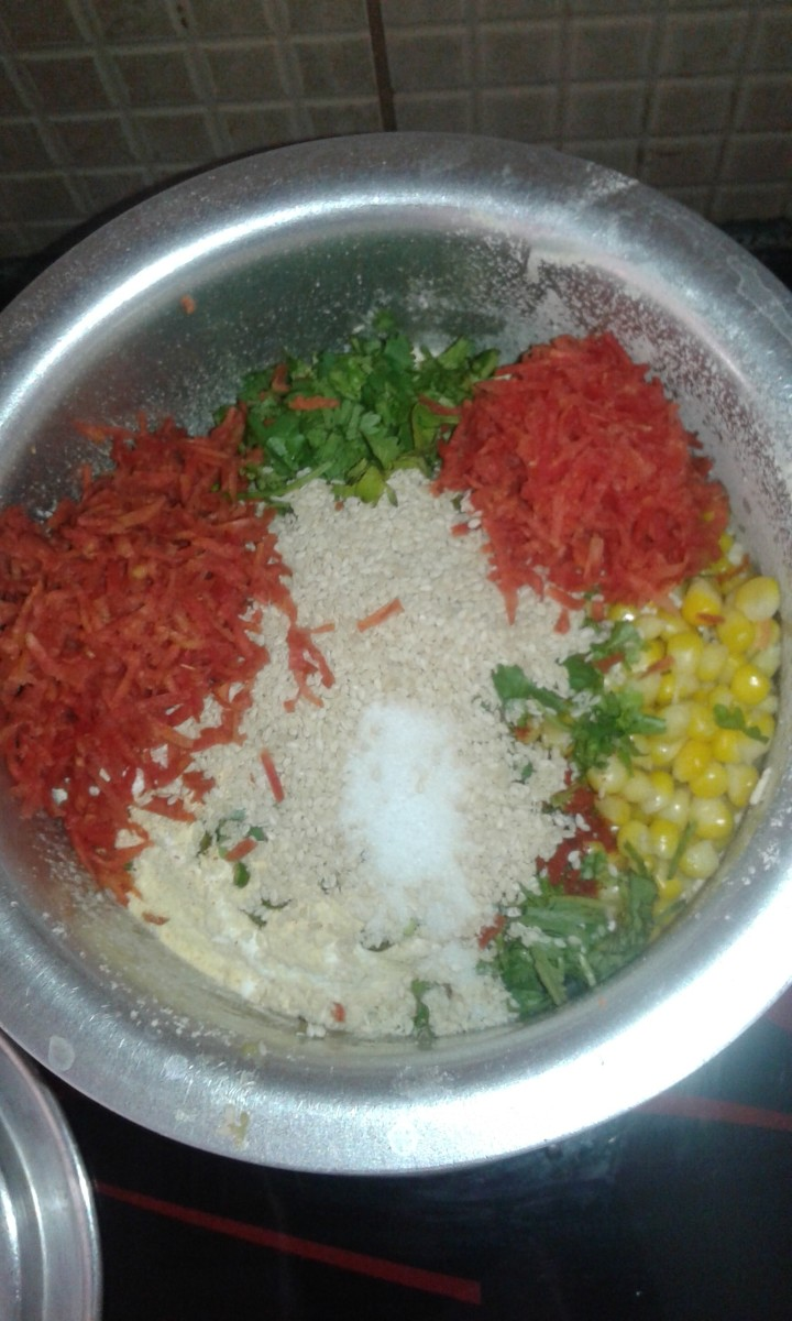 Add rice flour and gram flour. Mix it slightly and add grated carrot, chopped coriander, corn, chopped green chilli, ginger garlic paste, red chilli powder, cumin, sesame seeds and salt.
