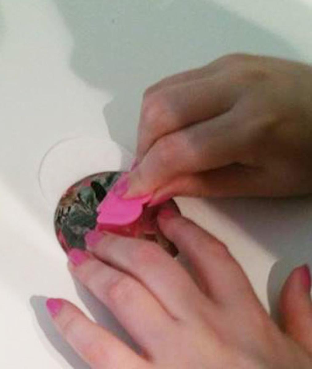 Scrape off excess nail polish...