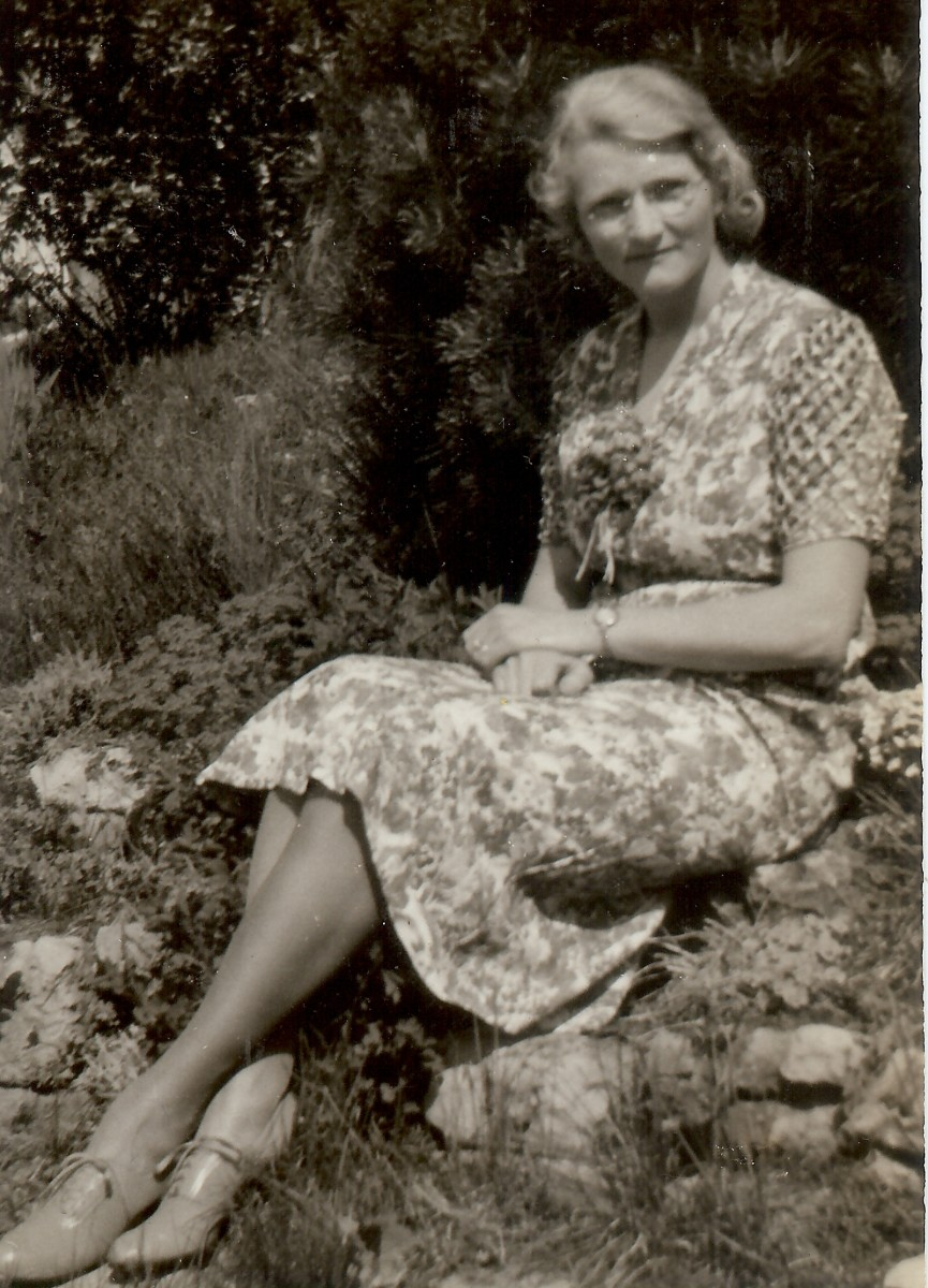 My paternal grandmother is sitting on a retaining wall of her rock garden going down to the lake.