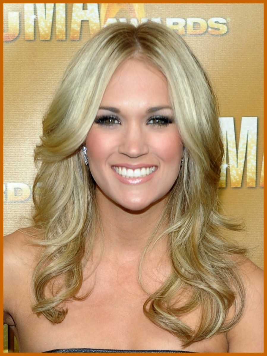 Carrie Underwood with light ash blonde hair, parted in the center, layered, and slightly flipped. Celebrities with Light Ash Blonde Hair Color.