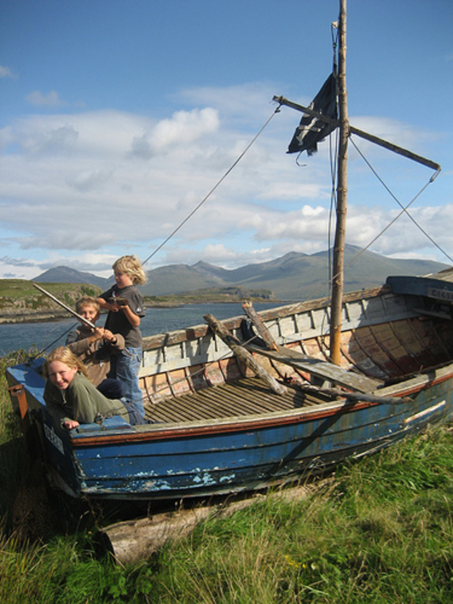 Children play on an old fishing ship near the harbour at Ulva.