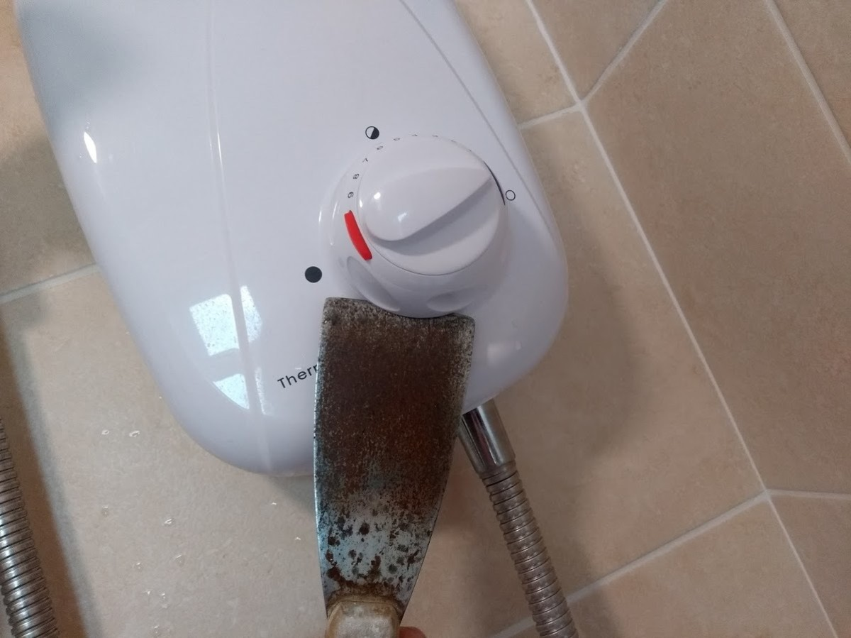 Use a flat tool such as a spatula or scraper to lever off the knob.