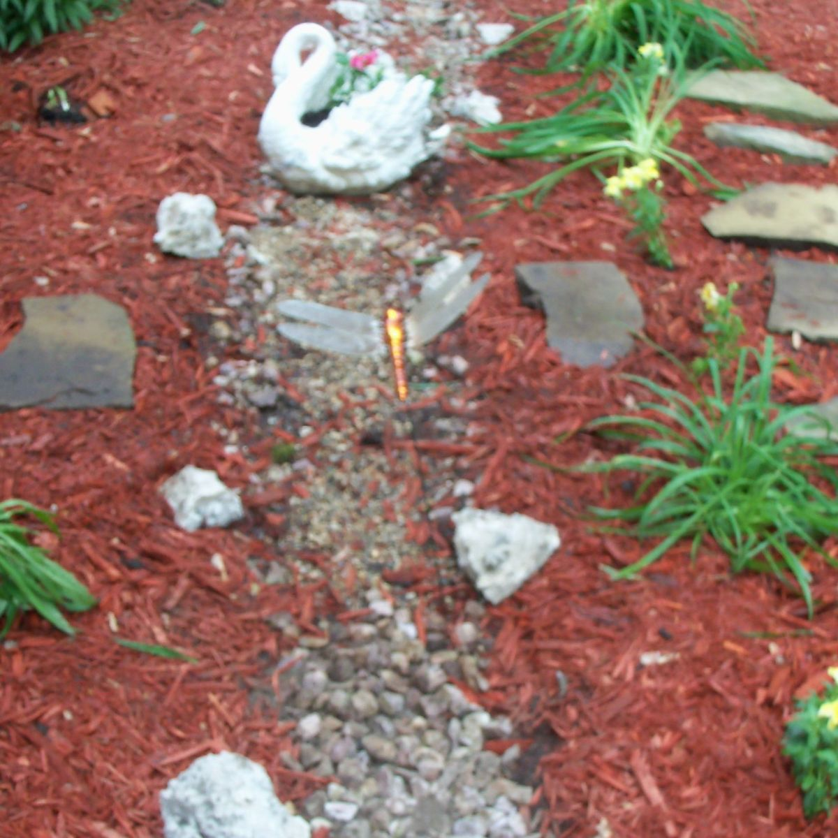added river rock, big pieces of brocken concrete and transplanted some day lilies and black-eyed-susans- added a swan planter