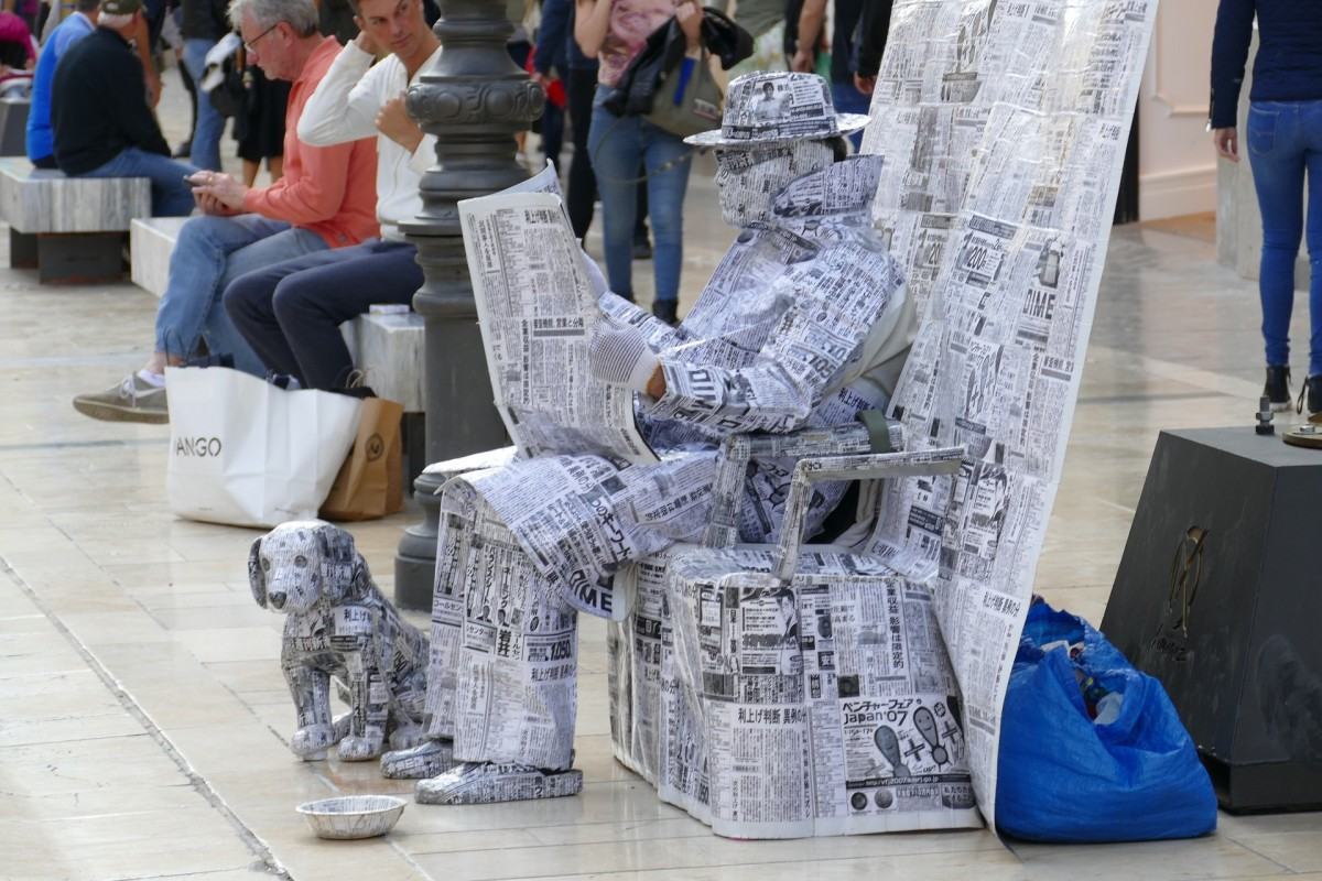 A man sitting in a chair reading a newspaper with his dog sitting at his feet. The entire realistic art and craft work is made of newspapers.