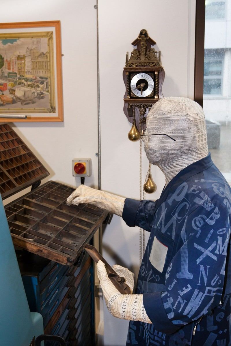 A paper mache man sitting in front of his wooden box organizer. .