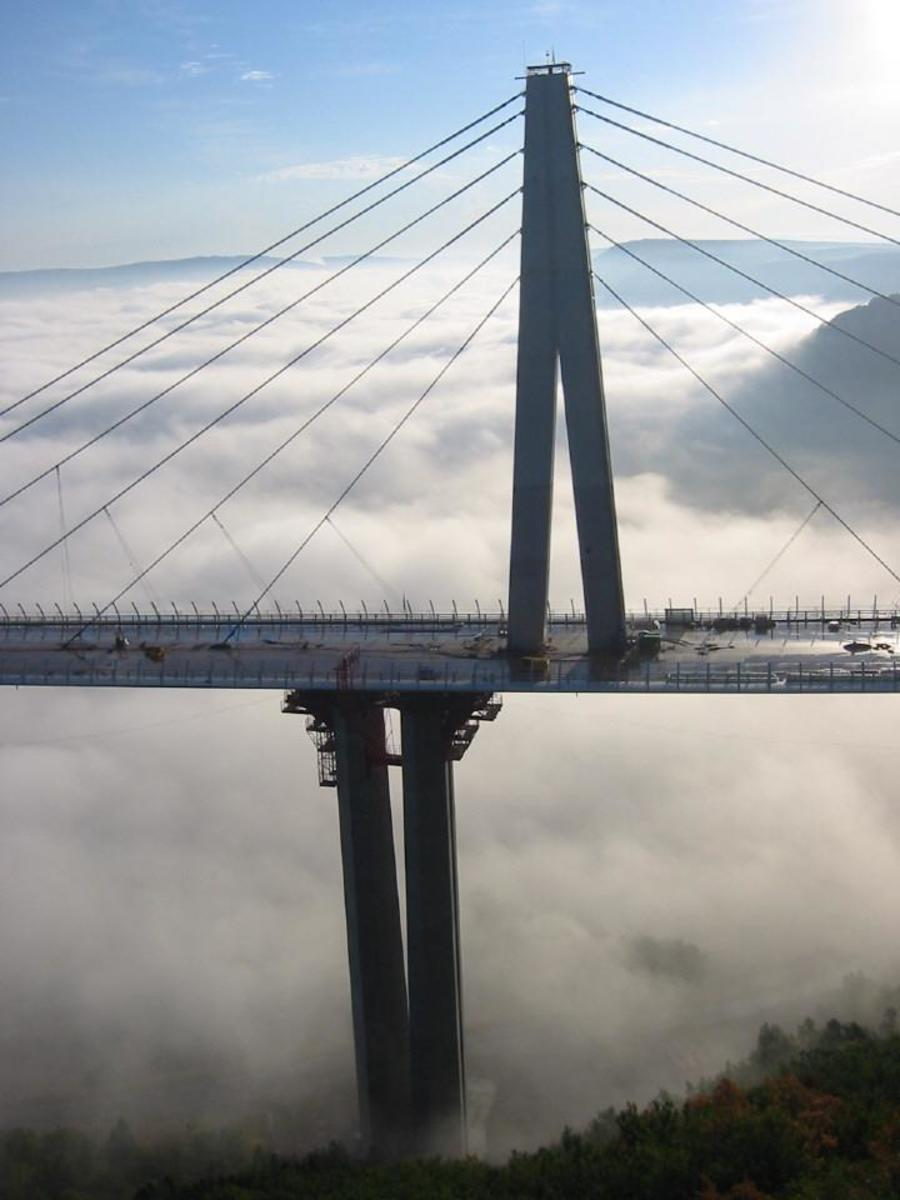Bridge with blue sky above and clouds below.