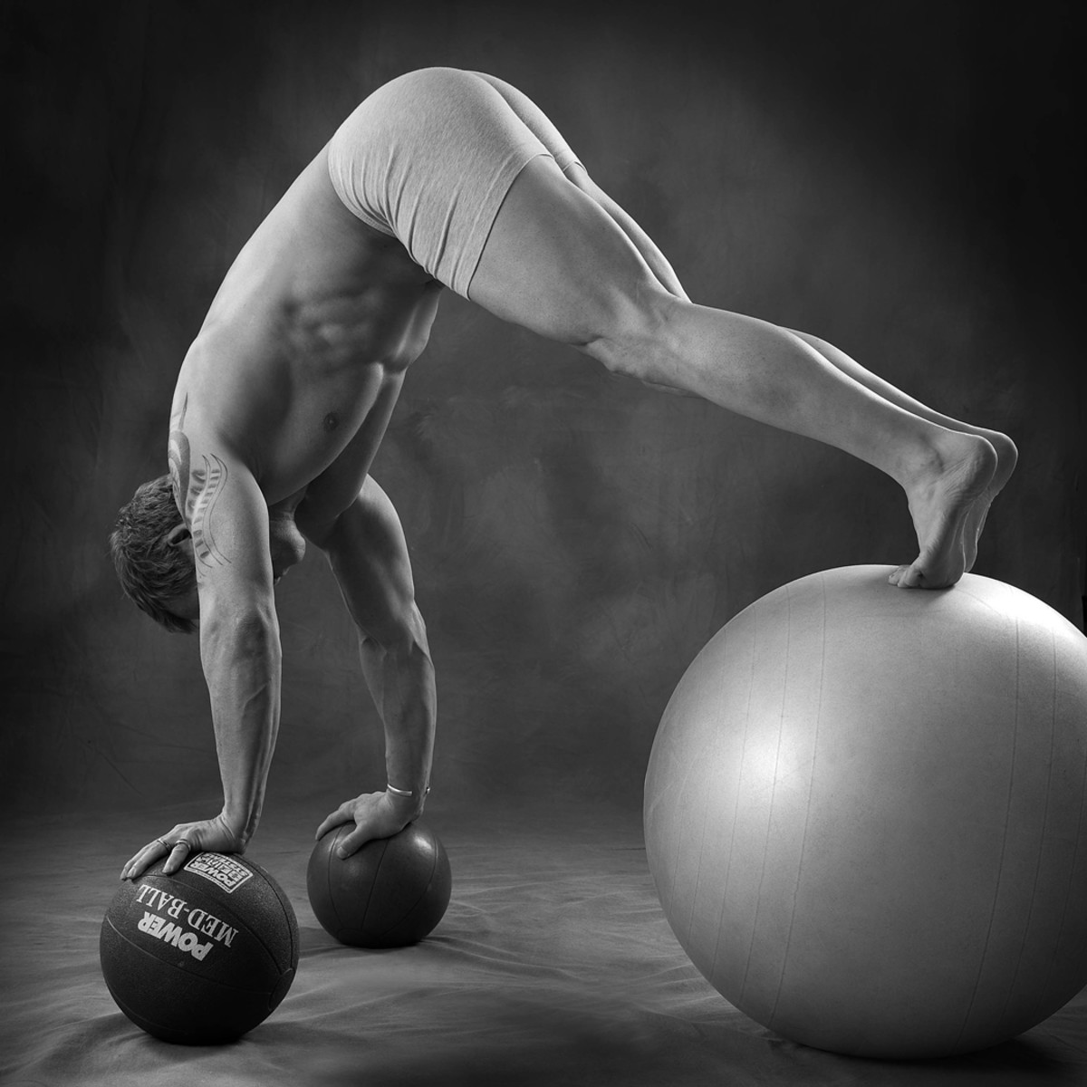 Author doing a push up/hip flexion on ball with hands on medicine ball. This is an advanced exercise that challenges the core muscles as well as the stabilizer muscles around the shoulder joint complex.