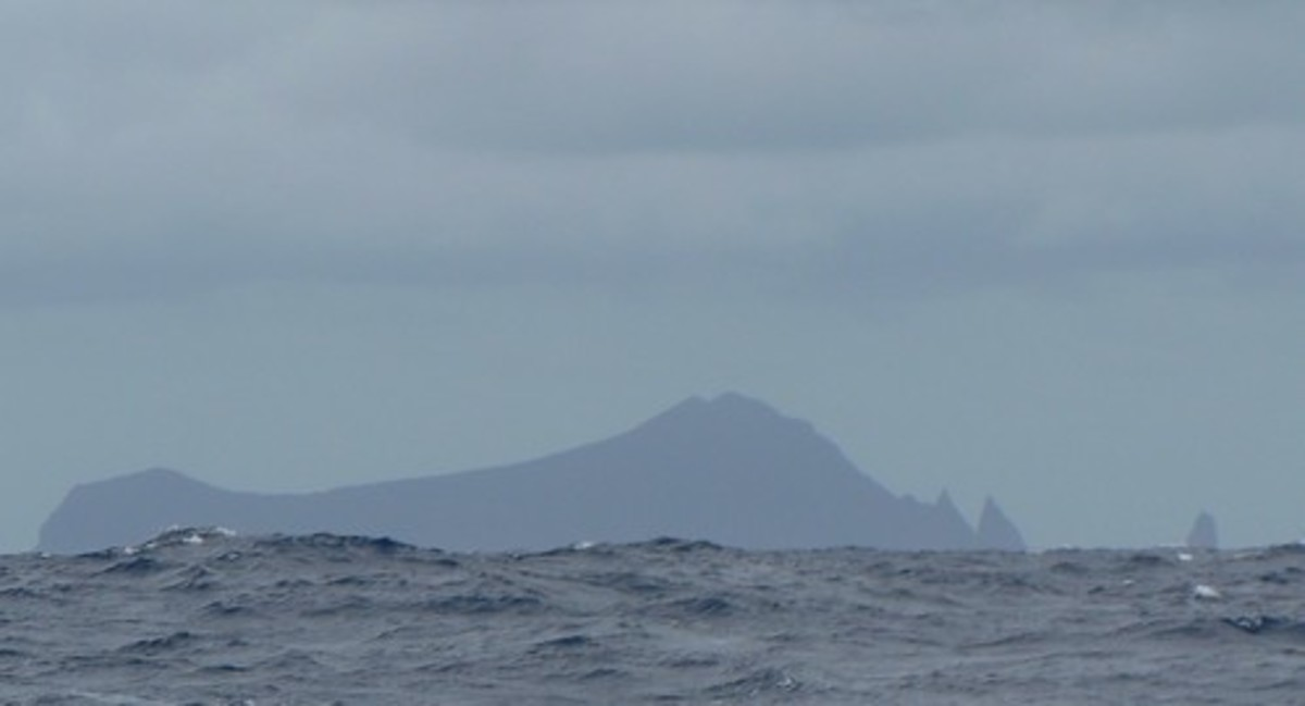 Isolated Ata Island rises from the gloom in the Pacific Ocean.