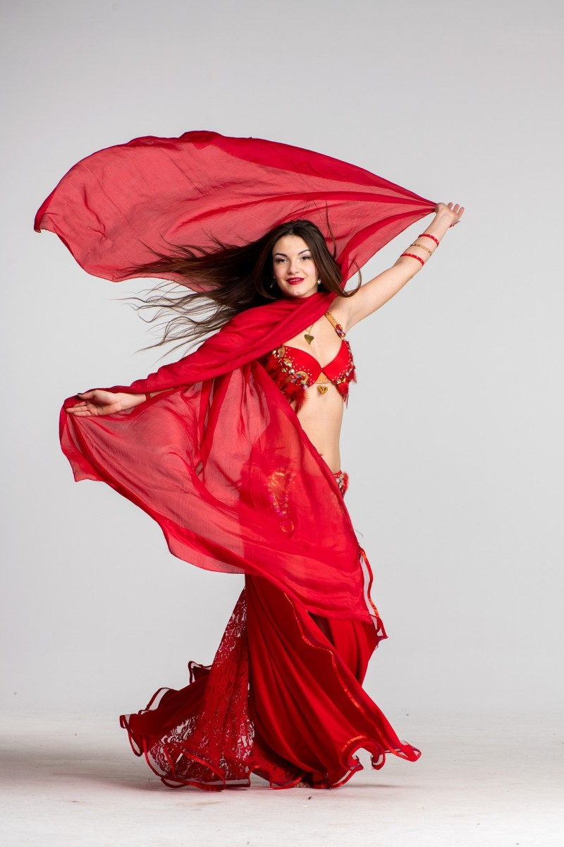 A beautiful belly dancer wearing a red Turkish costume.