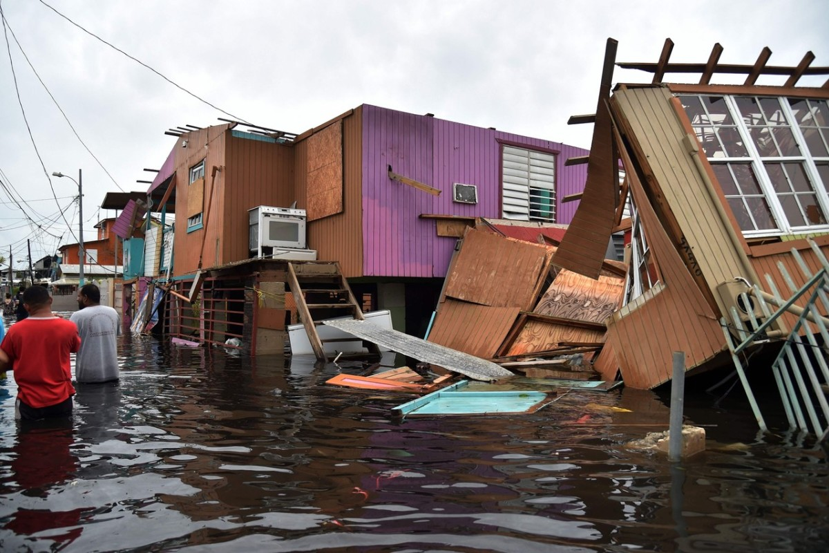 People walk through a flooded street among damaged houses left in the wake of Hurricane Maria in Cataño, Puerto Rico. HECTOR RETAMAL/AGENCE FRANCE-PRESSE/GETTY IMAGES