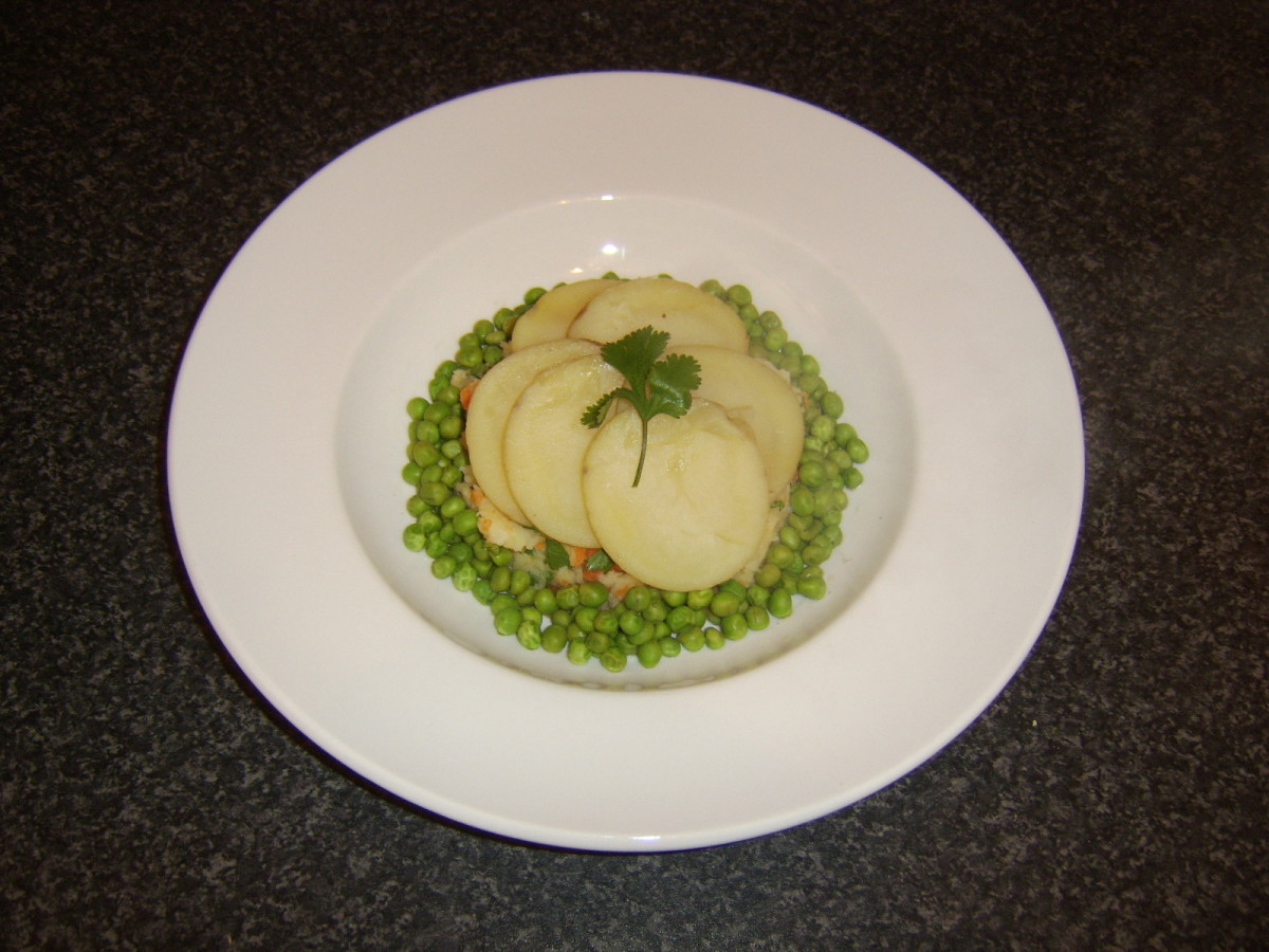 Vegan friendly scalloped potatoes served with carrot and parsnip mash and peas