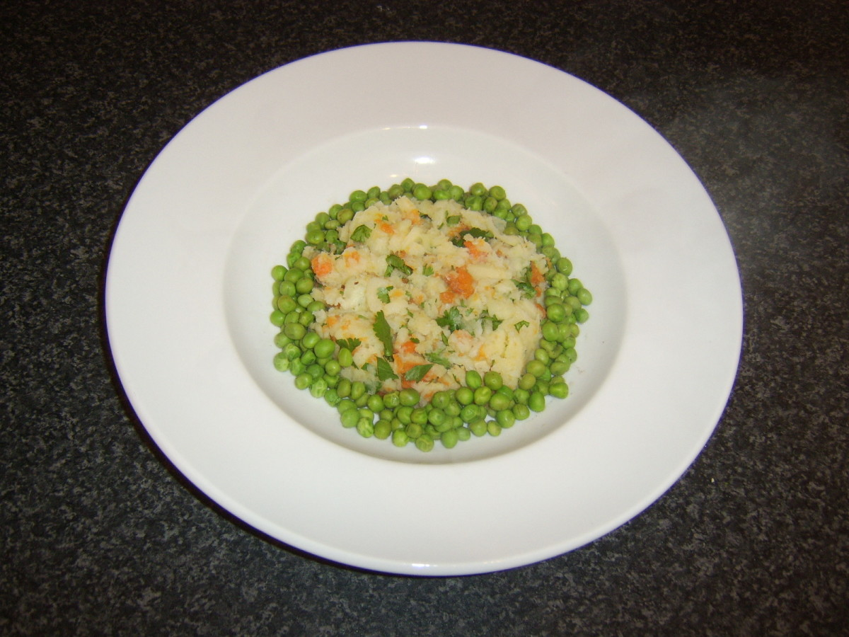 Peas are spooned around the carrot and parsnip mash