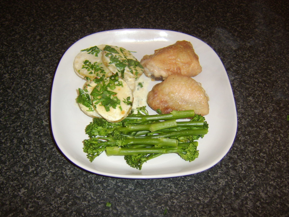 Stove top scalloped potatoes are served with roast chicken thighs and tenderstem broccoli