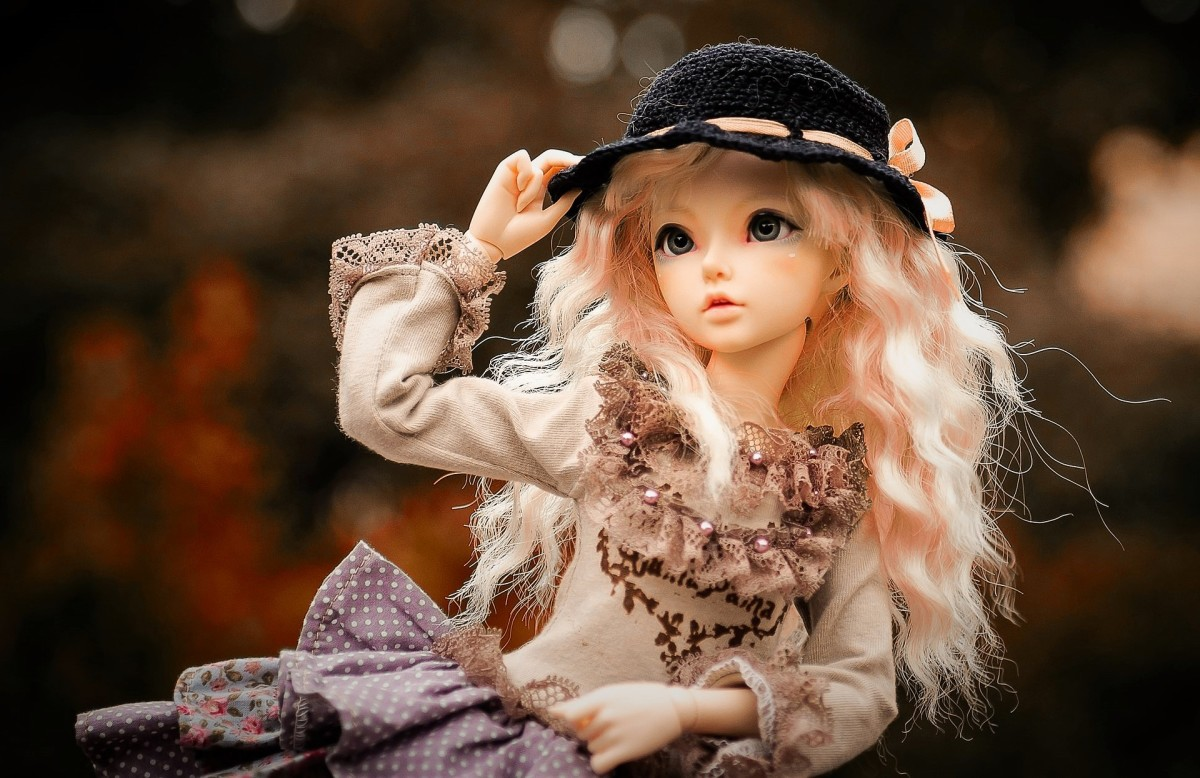 A doll wearing a black hat and funky clothing.