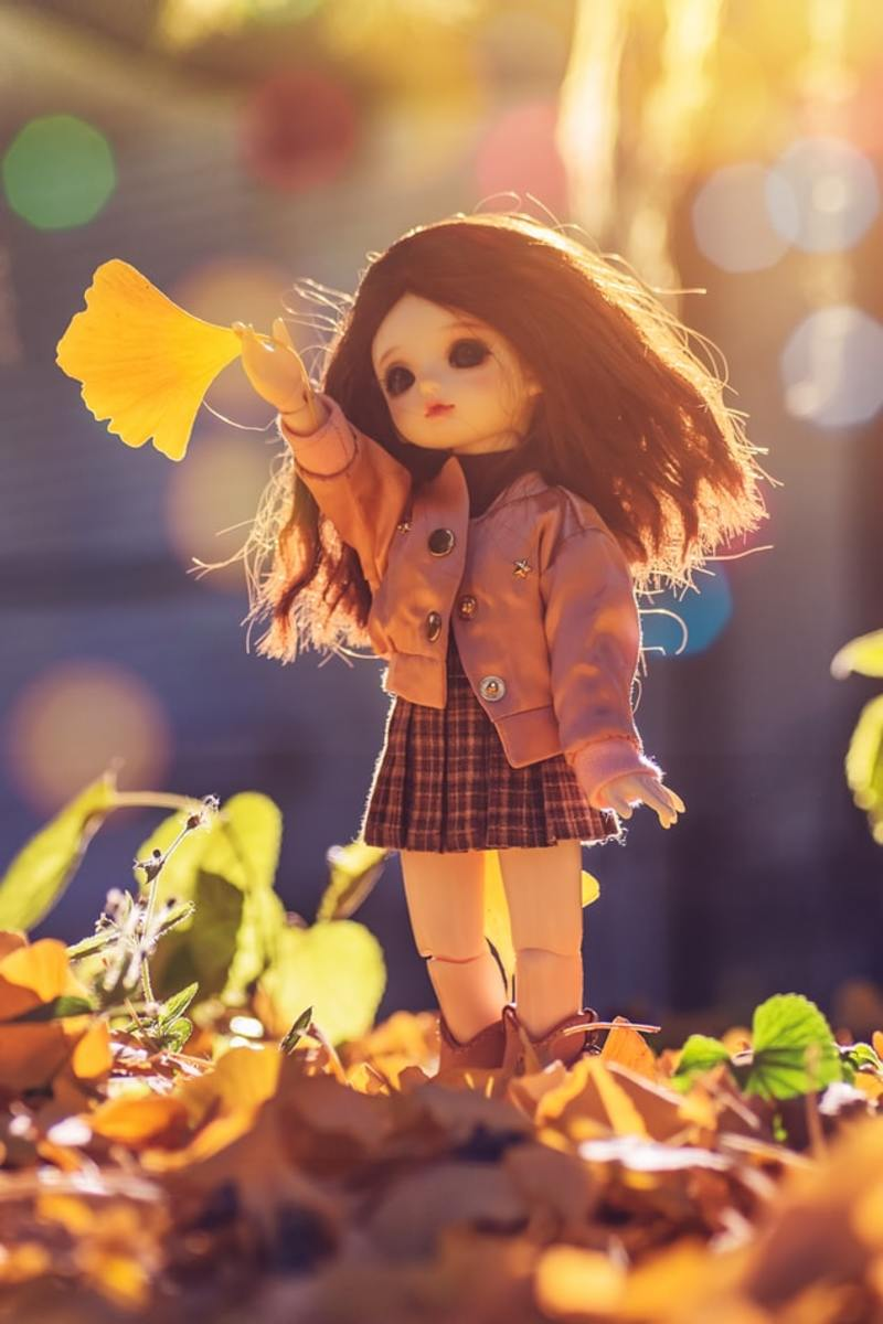 A doll standing on brown leaves is wearing an outfit of a brown skirt and jacket for the autumn weather.