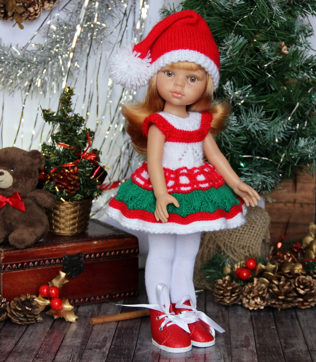 A baby doll wearing a crocheted Christmas dress and hat.