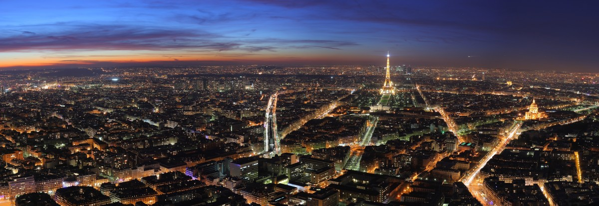 Paris at dusk.  The Eiffel Tower can be seen near the centre of the screen.  Note the reality low-rise nature of the buildings.  Photo by Benh LIEU SONG and distributed under GNU Free Documentation License Version 1.2.
